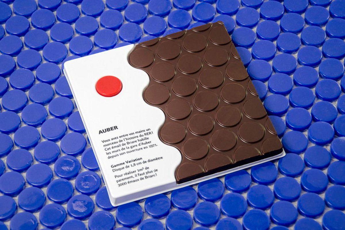 Chocolate bar shaped like a mosaic of circular tiles against a backdrop of blue circular tiles.