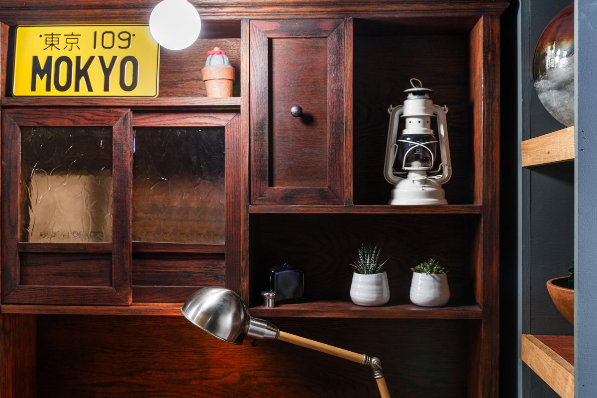 """A brown wooden bookshelf with a yellow """"Mokyo"""" license plate, a white lamp, and two succulents in white pots."""