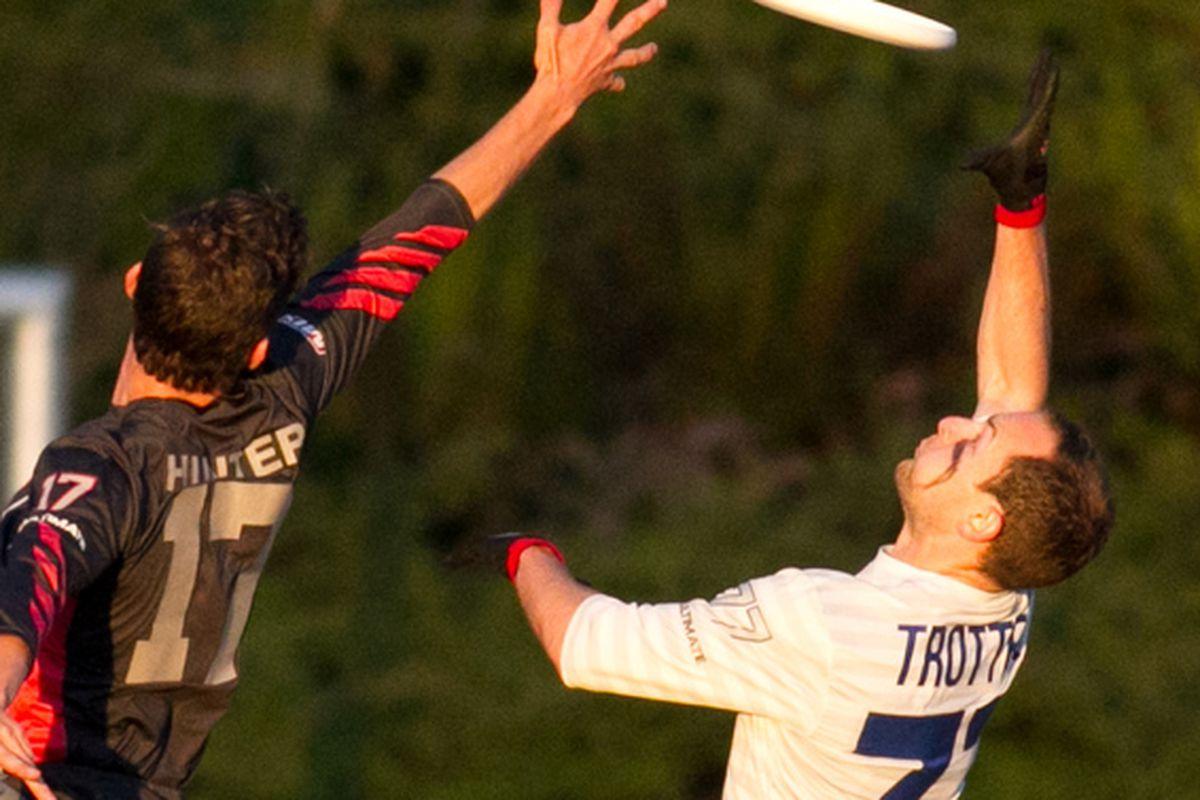 Elliot Trotter (right) skies for a disc against the Vancouver Nighthawks