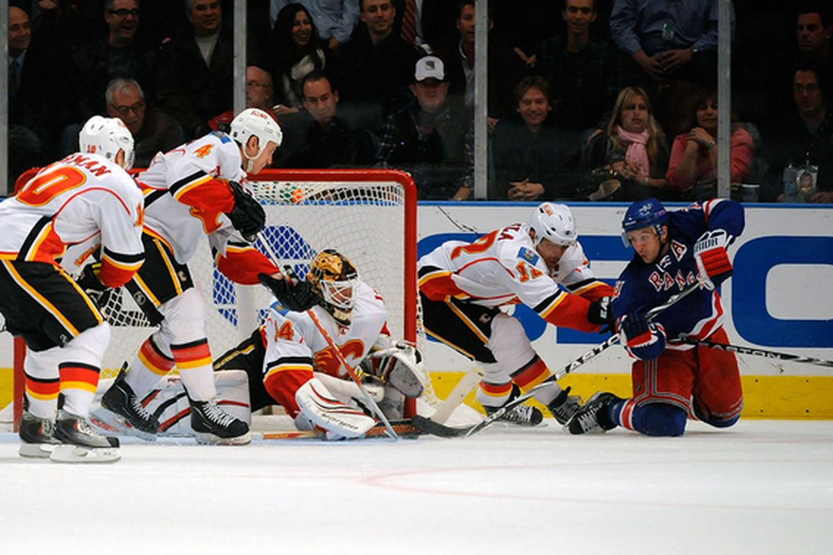 NEW YORK - NOVEMBER 22:  Mikka Kiprusoff #34 of the Calgary Flames makes a save against Ryan Callahan #24 of the New York Rangers on November 22 2010 at Madison Square Garden in New York New York.  (Photo by Lou Capozzola/Getty Images)