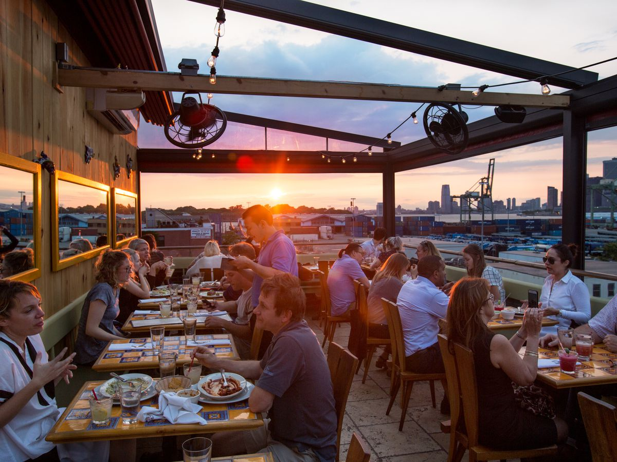 Customers are seated at an outdoor seating area at sunset with views of a city skyline in the background