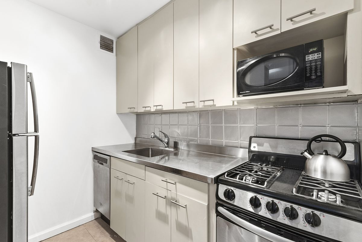 A kitchen with light grey cabinets.