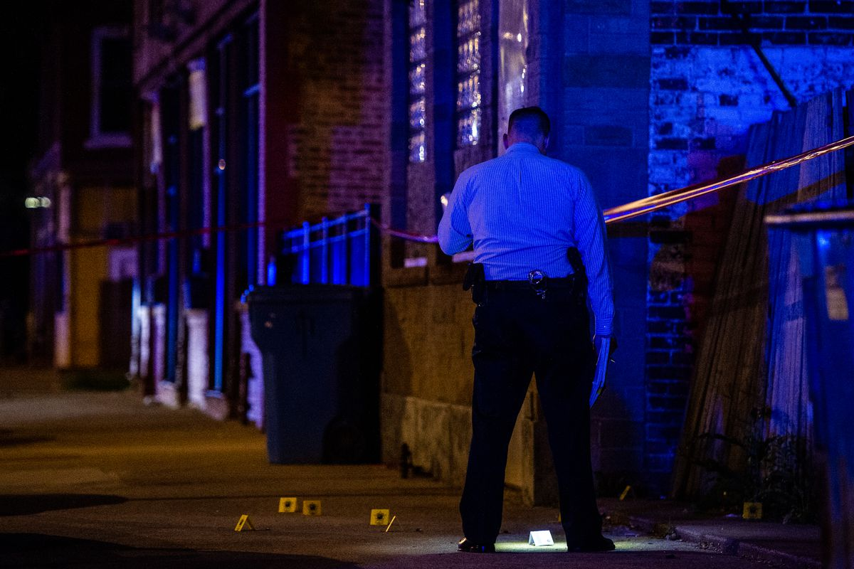 Police look for evidence on the sidewalk after the shooting.