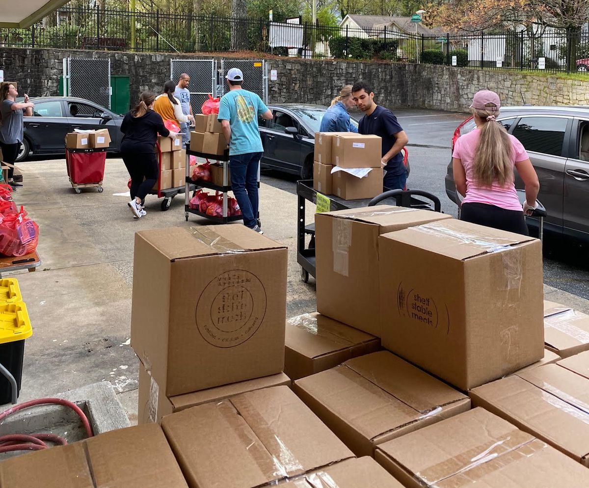 A group of workers move boxes full of meals to cars.