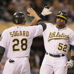 Oakland Athletics' Yoenis Cespedes (52) is congratulated by teammate Eric Sogard (28) on his three-run home run off Seattle Mariners relief pitcher Steve Delabar during the seventh inning of their baseball game in Oakland, Calif., Saturday, April 7, 2012. Seattle won the game 8-7.