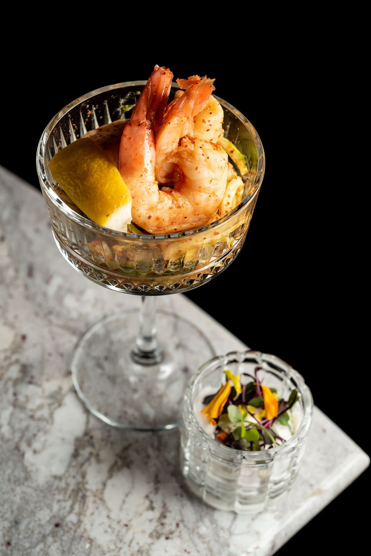 A shrimp cocktail in a tall glass, with edible flowers on the side.