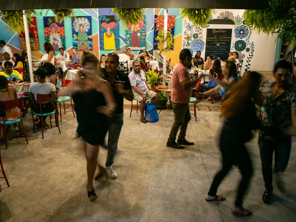 People dance in a dining room that has colorful pictures on the wall.