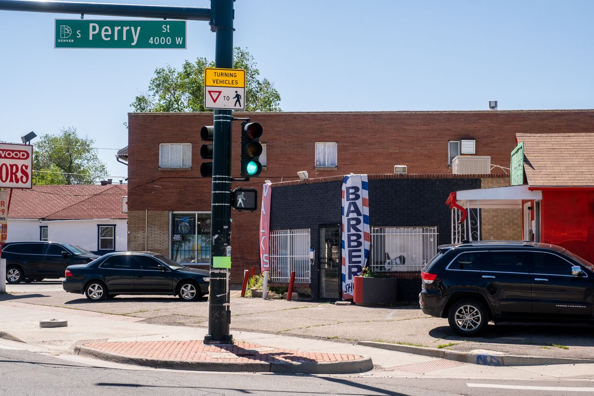 A barber shop sits on the corner of S Perry Street in Denver, just behind a large traffic light. Cars are parked along the side of the road.