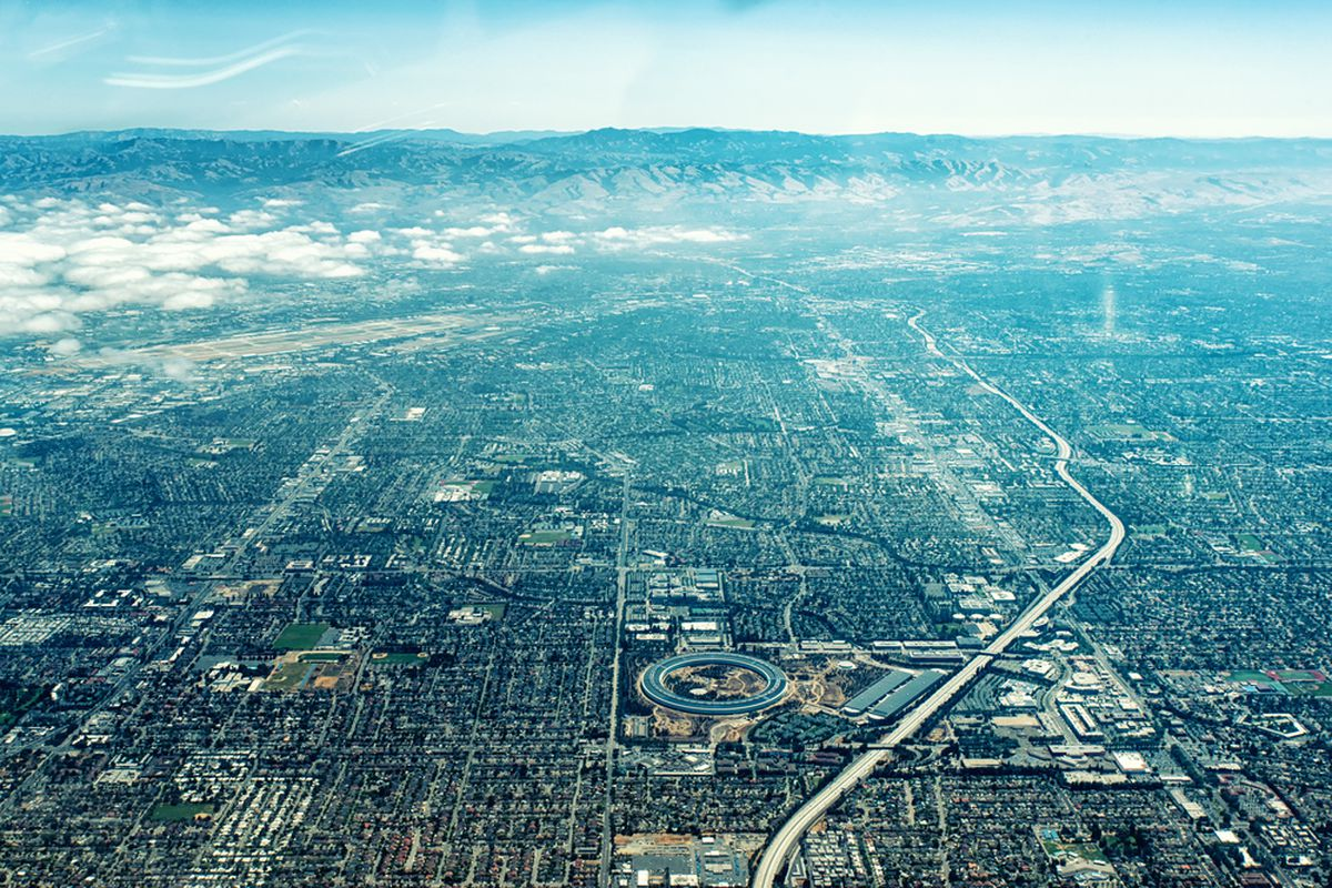 An aerial photo of Cupertino, with blue sky and clouds on the horizon and the huge, ring-shaped Apple complex prominently featured below.