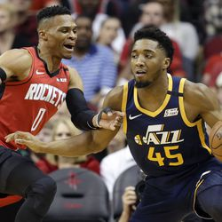 Utah Jazz guard Donovan Mitchell (45) dribbles as Houston Rockets guard Russell Westbrook defends during the first half of an NBA basketball game, Sunday, Feb. 9, 2020, in Houston.