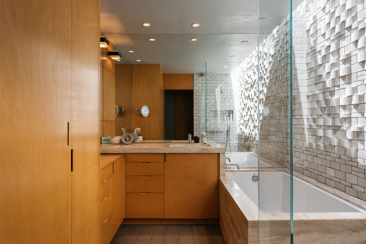 A bathroom with textured wall and honey-colored cabinets.