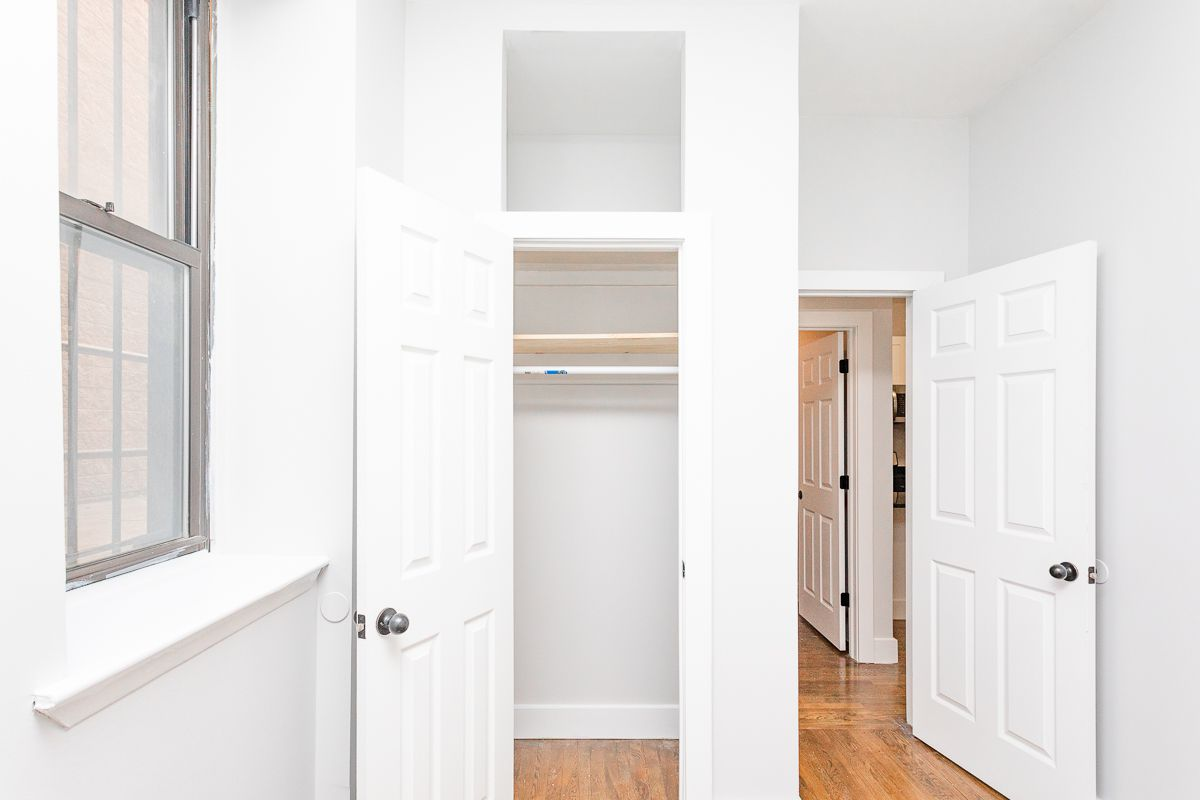 A bedroom with a small closet and hardwood floors.