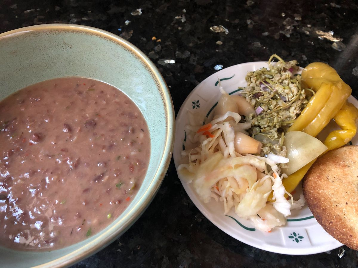 A teal bowl filled with red bean stew next to a white plate with an assortment of fermented vegetables arranged on it