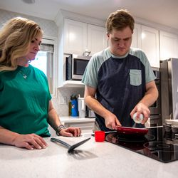 Jennie Dopp watches as son Jackson prepares a pan to fry an egg in their home in Layton on Friday, June 4, 2021. Jackson Dopp has autism and had been waitlisted for services for people with disabilities for many years, but the end's nowhere in sight.