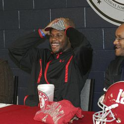 Bob Jones High School football player Reggie Ragland puts on an Alabama hat as mom Ann White and dad Reggie Ragland Sr., look on, after announcing his intentions to attend the University of Alabama and play football during national signing day, Wednesday, Feb. 1, 2012, at Bob Jones High School in Madison, Ala.