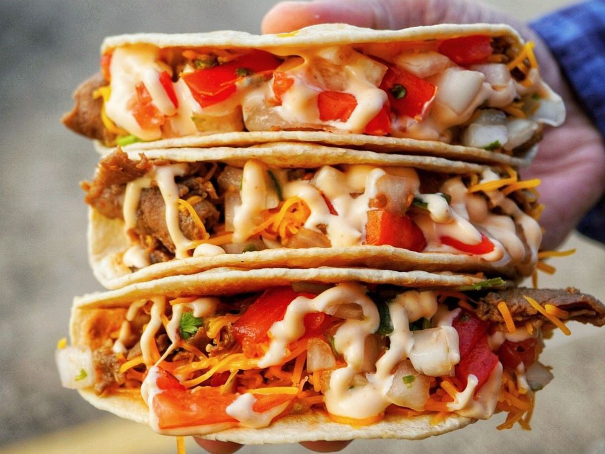 a hand holding three tacos stuffed with culgogi, tomatoes, cheese and sauce