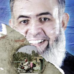 In this March 23, 2012 picture an Egyptian is seen through a defaced poster for Egyptian presidential candidate Hazem Abu Ismail, a prominent Salafist, center, in Cairo, Egypt. An ultraconservative Islamist presidential hopeful who may be disqualified from the race after it was announced that his mother was an American citizen.The presidential election scheduled in May will mark the beginning of a handover of power by the ruling military to an elected civilian, following last year's popular uprising that overthrew Hosni Mubarak. (AP Photo/Amr Nabil)