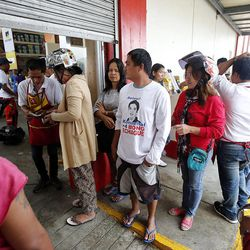 People line up to purchase materials as a hardware store is the first to re-open in Tacloban, Friday, Nov. 22, 2013 following a typhoon.