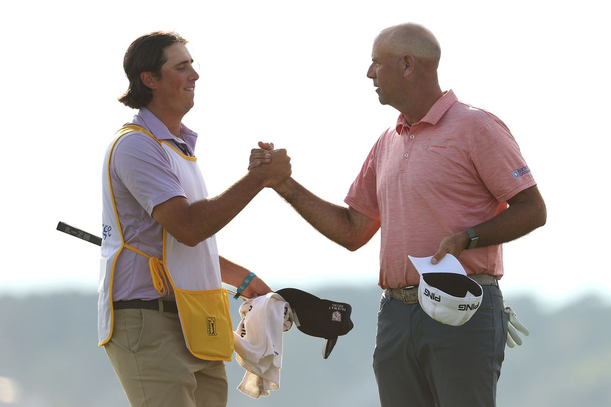 Stewart Cink of the United States shakes hands with his caddie and son, Reagan Cink, on the 18th green after completing their third round of the RBC Heritage on April 17, 2021 at Harbour Town Golf Links in Hilton Head Island, South Carolina.