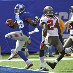 New York Giants wide receiver Hakeem Nicks (88) runs past Tampa Bay Buccaneers strong safety Mark Barron (24) for a touchdown during the first half of an NFL football game on Sunday, Sept. 16, 2012, in East Rutherford, N.J.