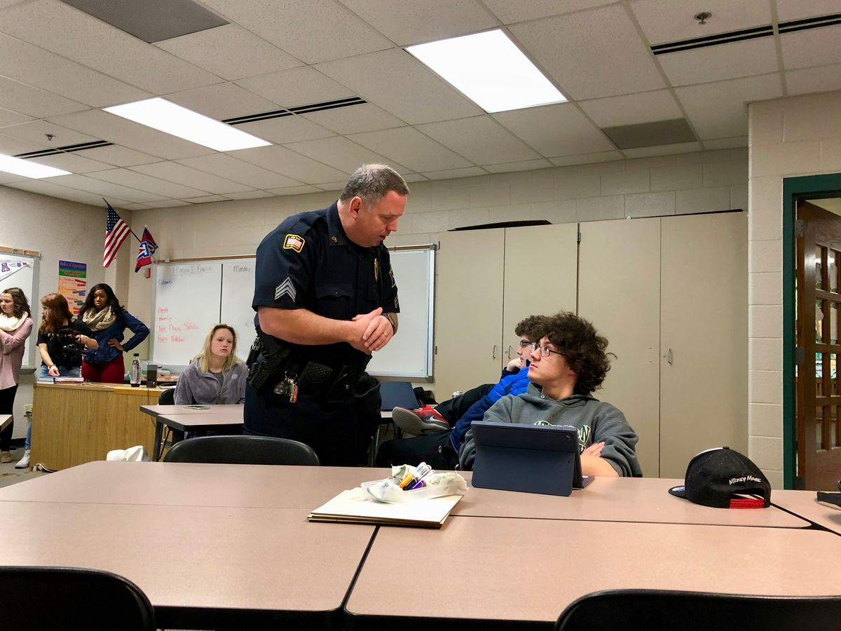 A local police officer answers questions during the financial Algebra 2 class at Noblesville High School.