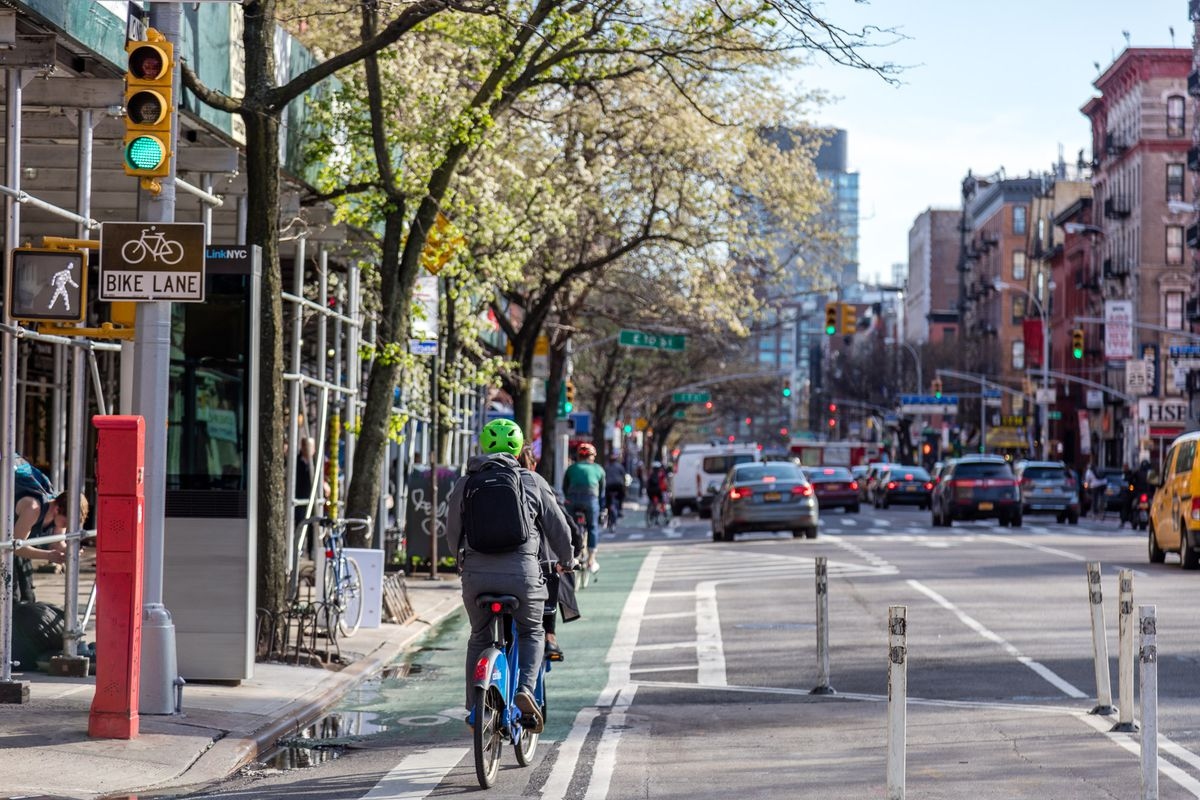 A cyclist in a lime green helmet rides on a protected bike lane in the East Village towards East 10th Street.