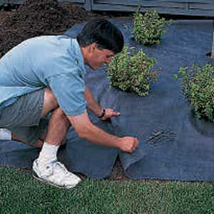 Man Overlaps Fabric Pieces To Prevent Weeds From Growing