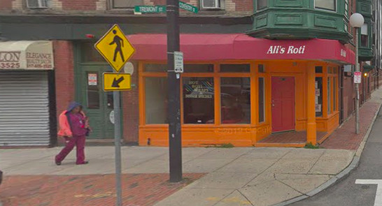 Exterior of Ali's Roti in Dorchester, with a bright orange exterior and red awning