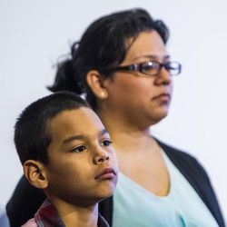 Eric Guadarrama, 10, stands with his mother, Grisel, before she speaks about her inability to afford health coverage for her family during a press conference at the state Capitol in Salt Lake City on Tuesday, Aug. 18, 2015.