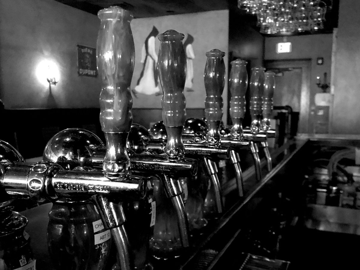 Black and white photo of tap handles at a bar