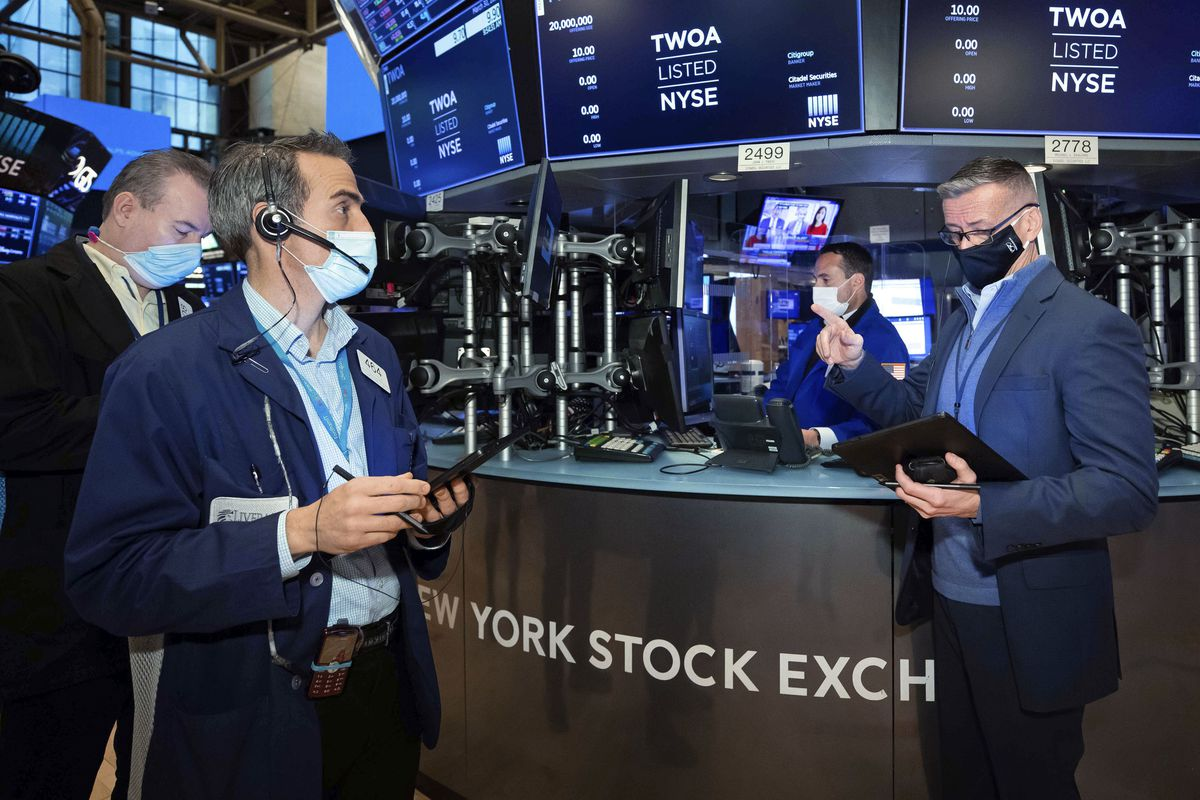 In this photo provided by the New York Stock Exchange, traders Gregory Rowe, foreground left, and Neil Catania, right, work on the floor. Tuesday, March 30, 2021.