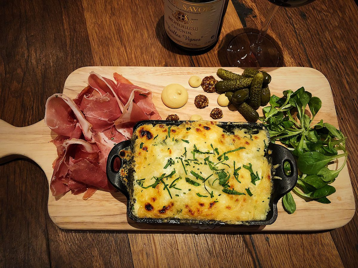 cast iron of raclette with pile of charcuterie and greens