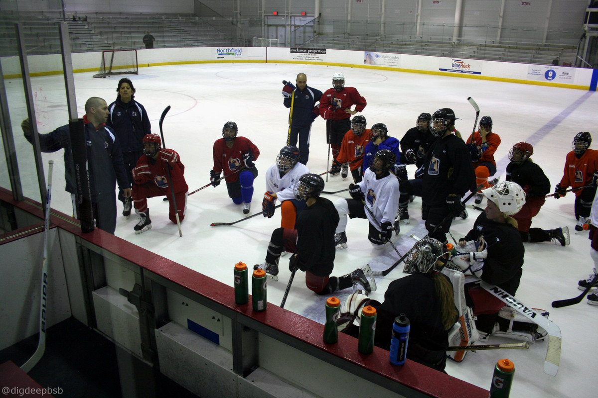 Riveters on ice with coaching staff