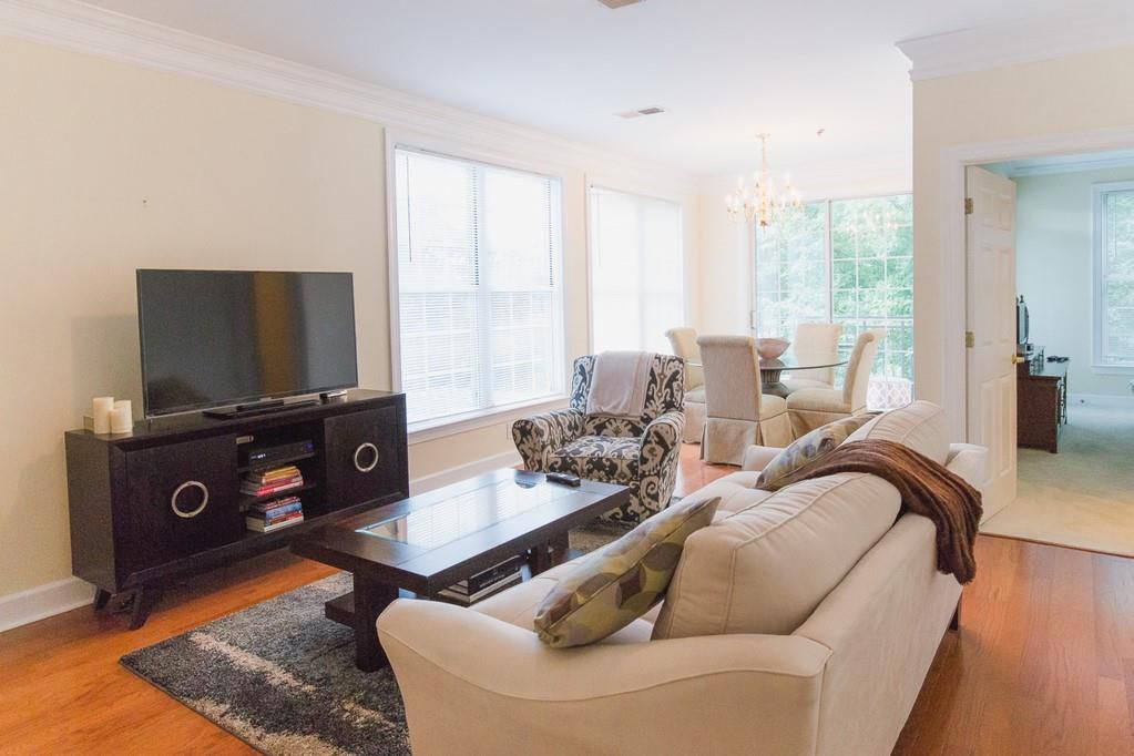 Living room with couch, chairs, coffee table, area rug, and entertainment stand with TV.