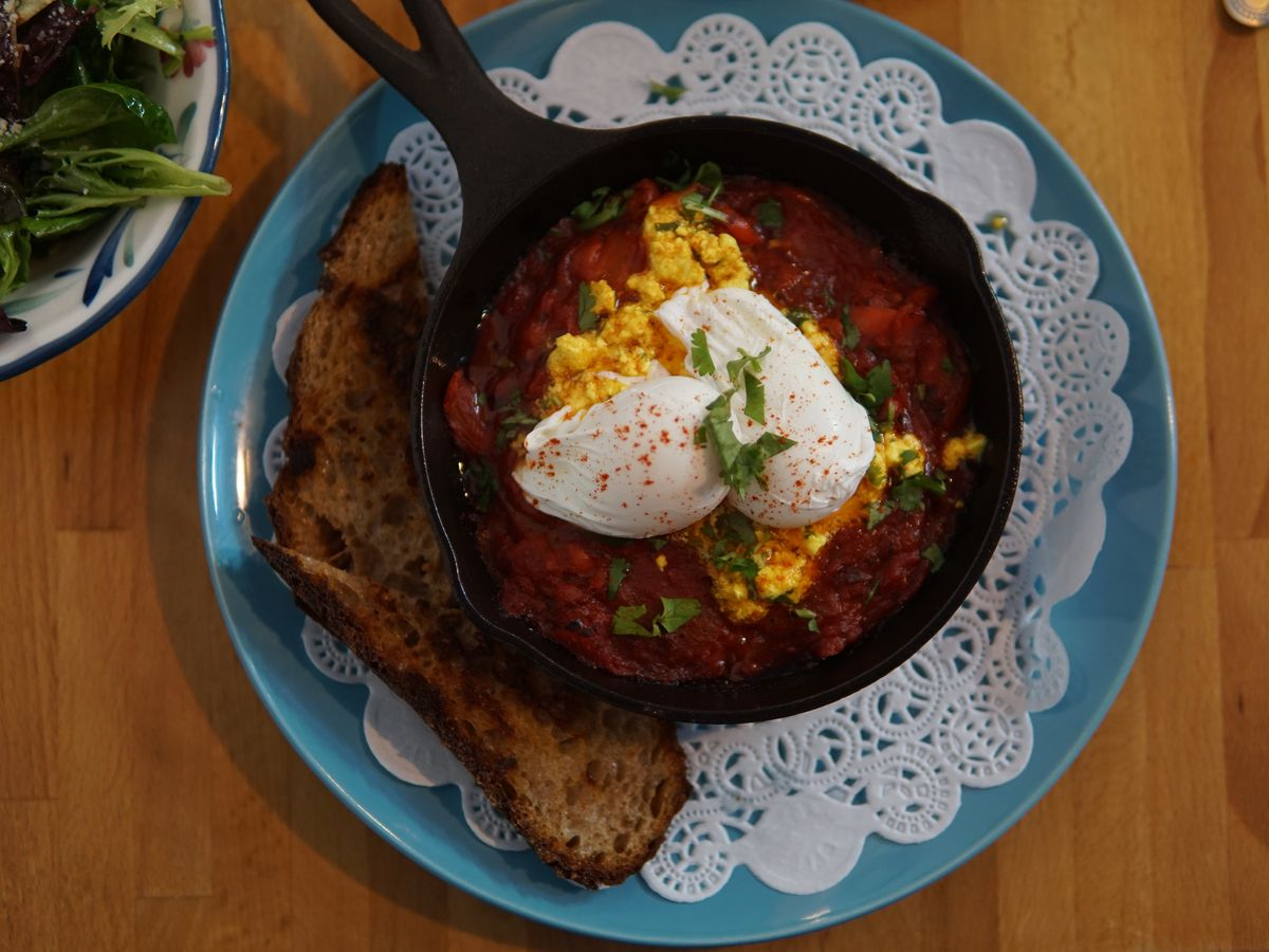 Two poached eggs sit in a cast-iron skillet, which sits on a blue plate with a doily and two pieces of toast