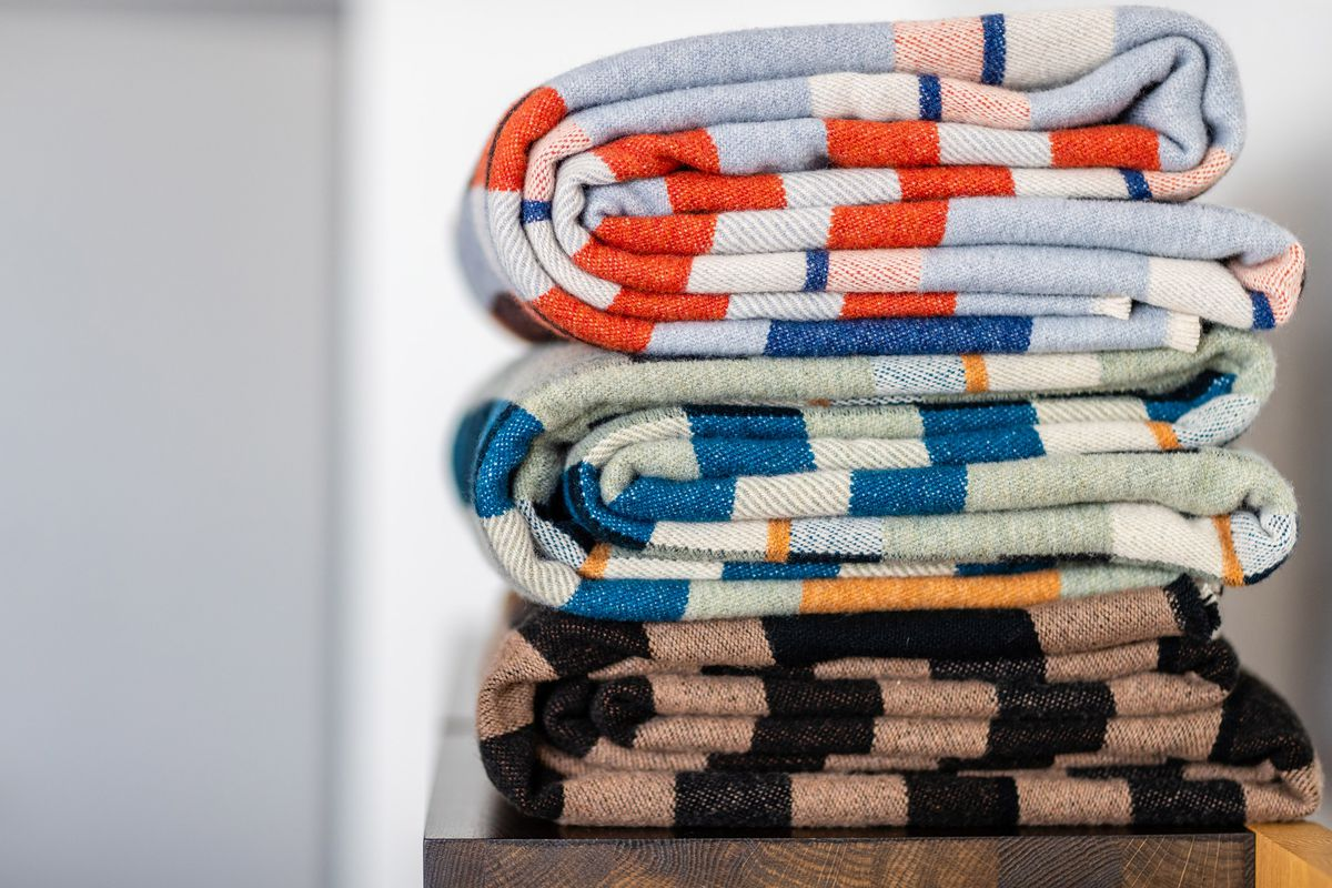 A pile of folded colorful striped blankets.