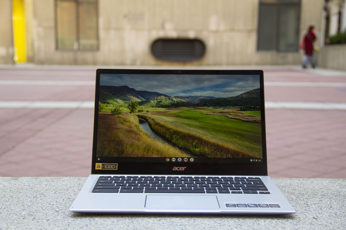 The Acer Chromebook Spin 513 sits on a stone bench, open. The screen displays a pastoral scene.