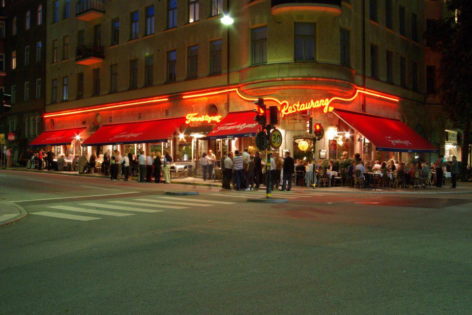 A crowd outside a corner restaurant with broad red awnings over sidewalk seating and bright neon signs with the name Tennstopet