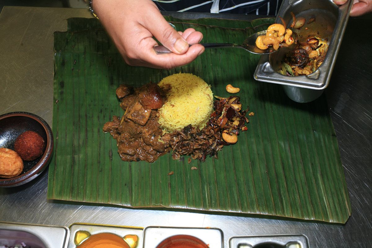 A chef spoons spiced, dry-toasted cashews on to the banana leaf of a lamprais