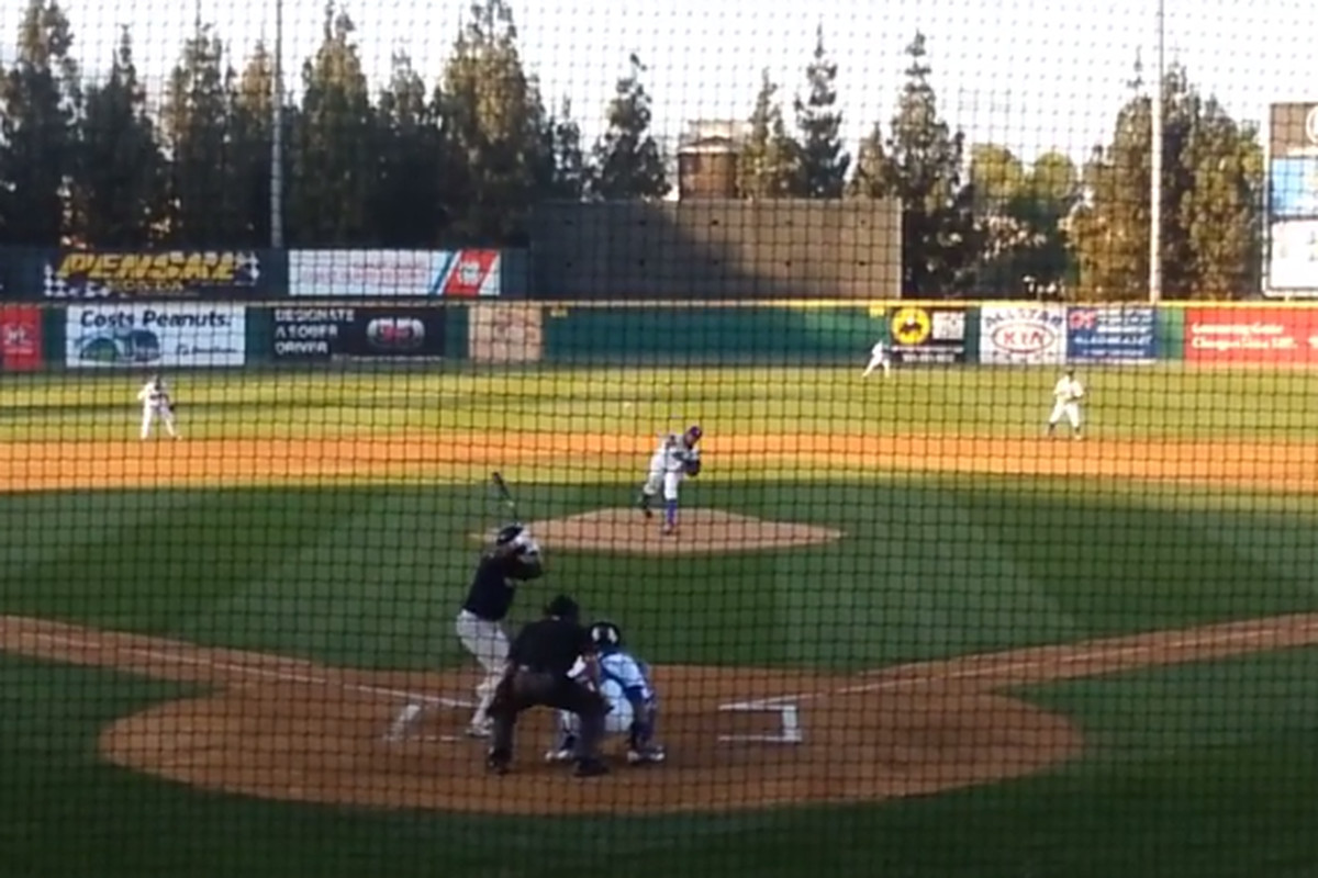 Carlos Frias delivers a pitch to Addison Russell