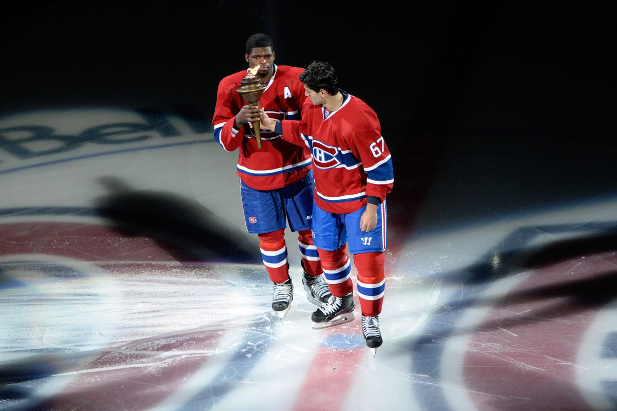 Oct 16, 2014; Montreal, Quebec, CAN; Montreal Canadiens forward Max Pacioretty (67) hands over the torch to teammate P.K. Subban (76) during the introduction ceremony before the game against the Boston Bruins at the Bell Centre. The Canadiens won 6-4