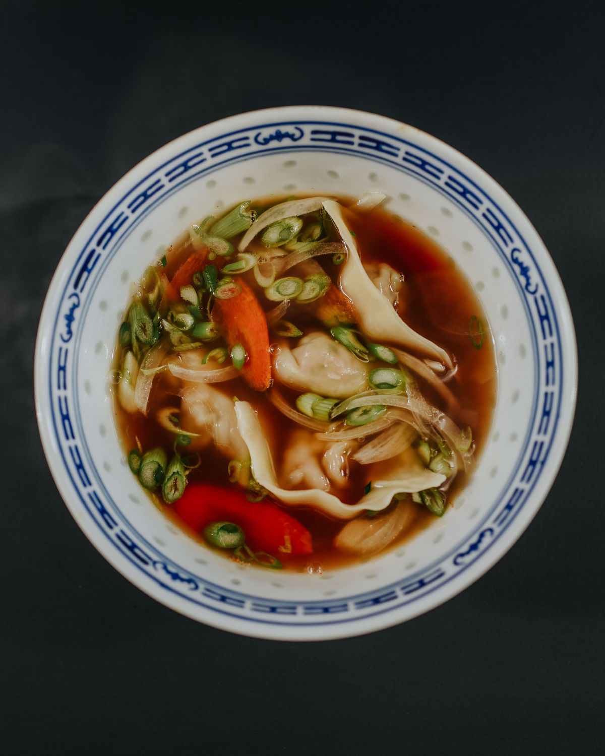 A bowl of wonton soup swimming in dark brother with scallions and carrots from Mow's Chinese Kitchen in Alpharetta GA