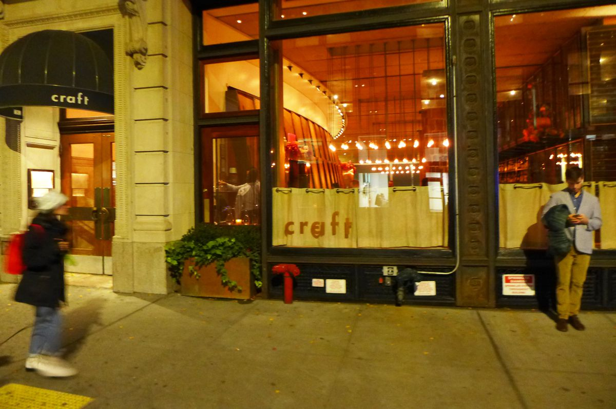 The restaurant's interior is seen thrown the window as a warm glow from outside, with two passersby.
