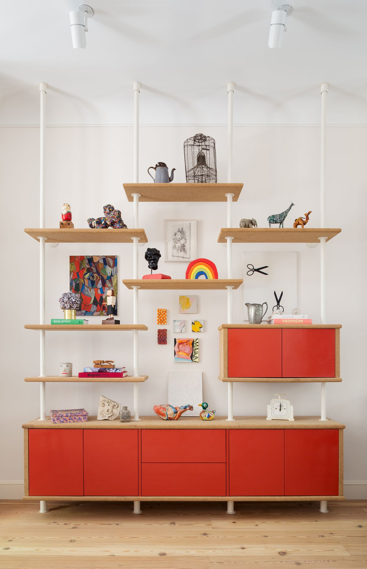 A shelving unit which has red drawers and wooden shelves. On the shelves are various objects.