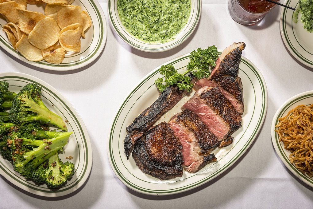 An aerial photograph of plates of steak, broccoli, spinach dip, and thick-cut potato chips