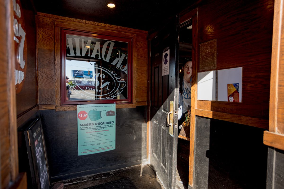 A woman walks out of the door at McShane's next to a sign that warns about mask policies.