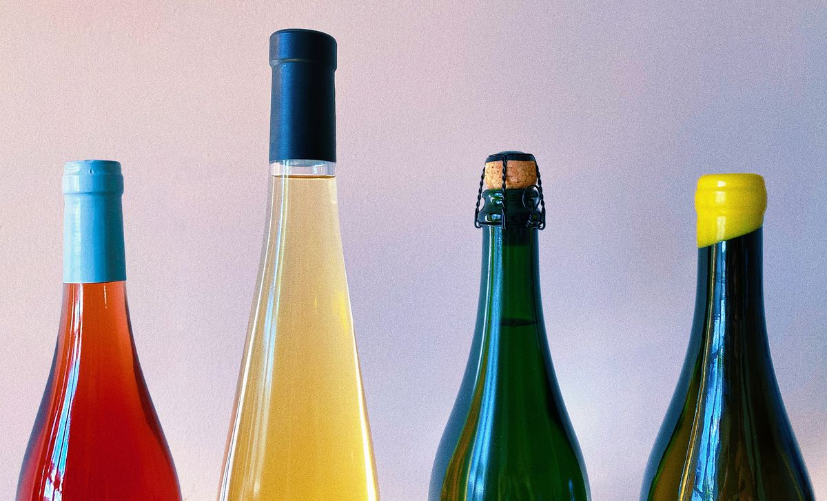 The upper half of four bottles of wine, with tops of different sizes, heights, and colors