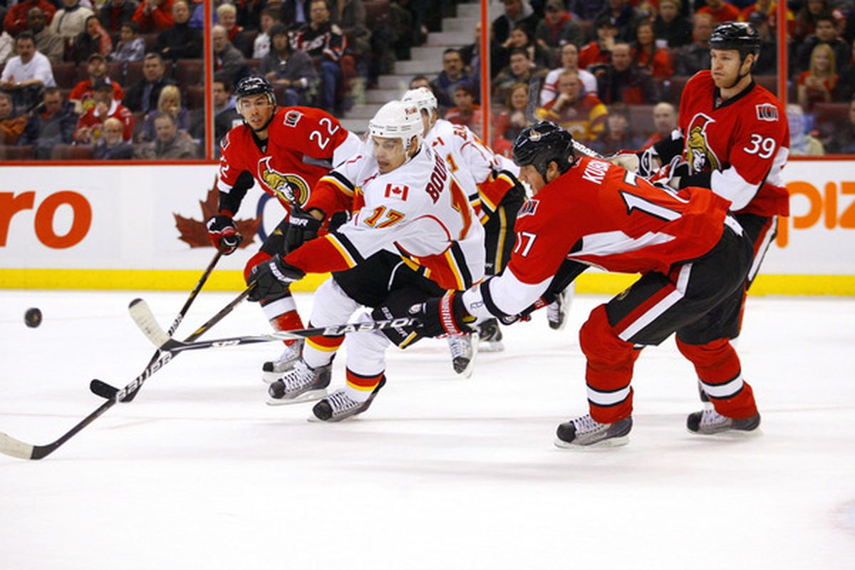 OTTAWA ON - JANUARY 14:  Filip Kuba #17 of the Ottawa Senators chips the puck away from Rene Bourque #17 of the Calgary Flames in a game at Scotiabank Place on January 14 2011 in Ottawa Canada.  (Photo by Phillip MacCallum/Getty Images)