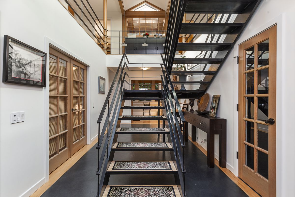 A black steel staircase rises from a hallway on a first floor to the second floor.