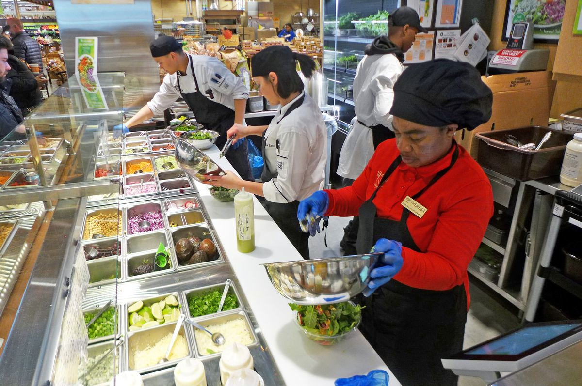 A line of three employees standing before a plethora of tubs containing vegetables and other ingredients put salads together and dress them.